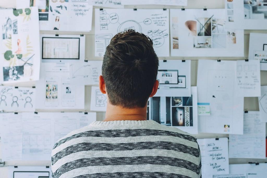 Mężczyzna patrzący na listy zadań i diagramy przyczepione do ściany.