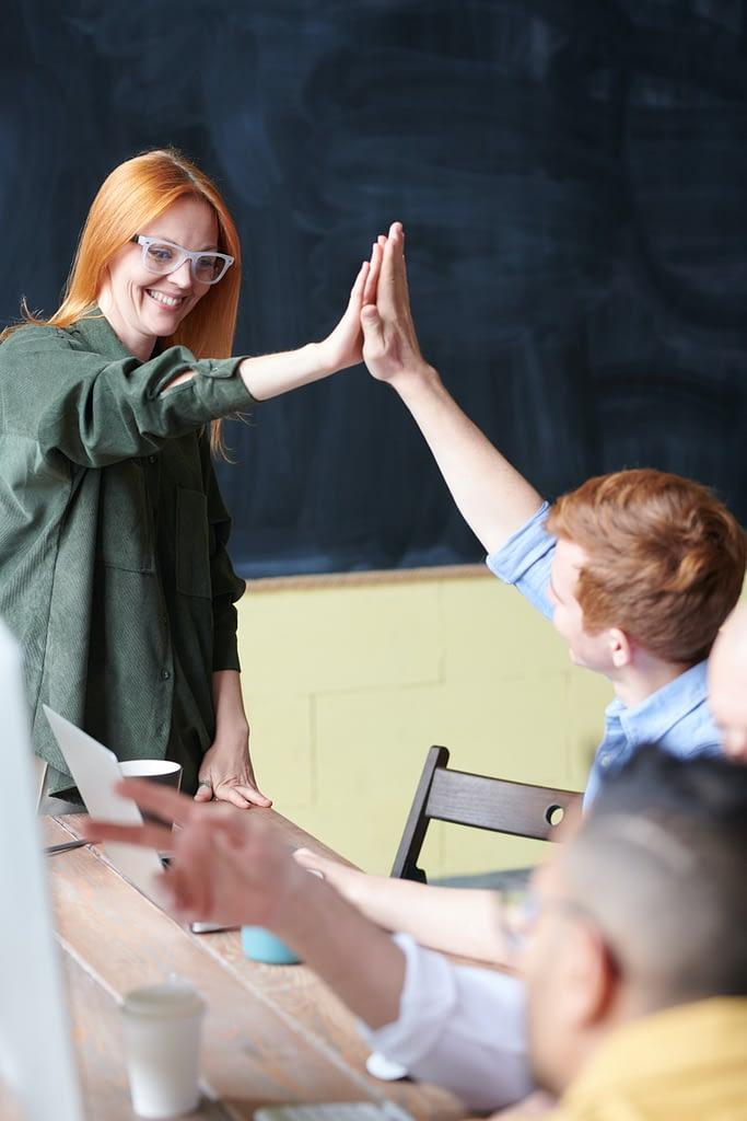 Nauczycielka przybija piątkę z uczniem. Angielski z native speakerem