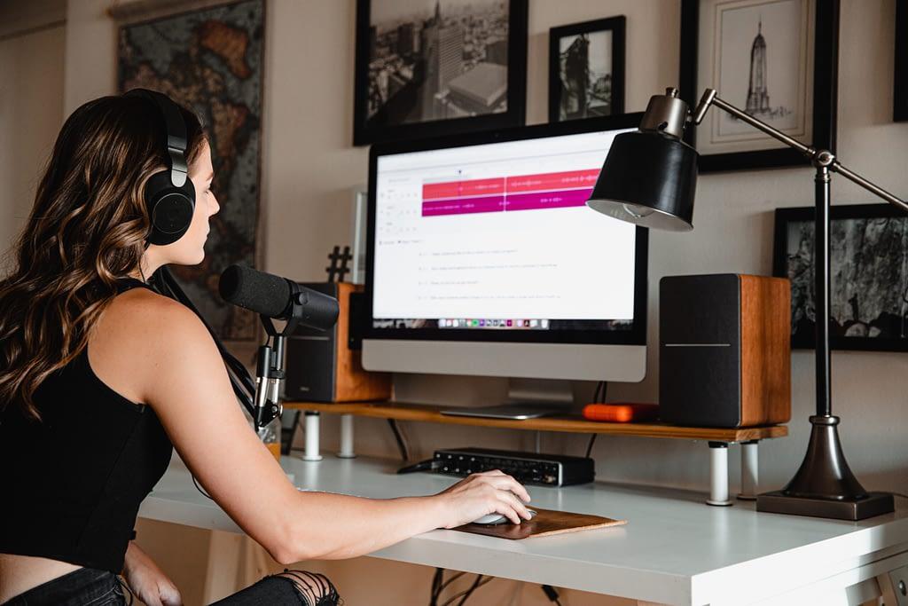 kobieta siedząca w słuchawkach przed komputerem, nagrywająca podcasty po angielsku